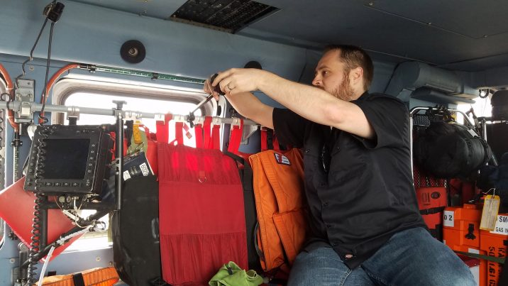 Matt Rowell testing a back to back GoPro mount inside of an MH60 Helicopter at Air Station Astoria.