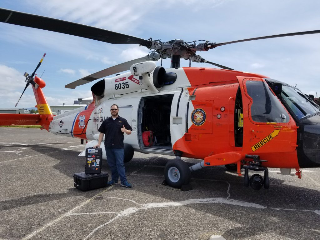 Matt Rowell posing with a USCG MH60 helicopter at Air Station Astoria.